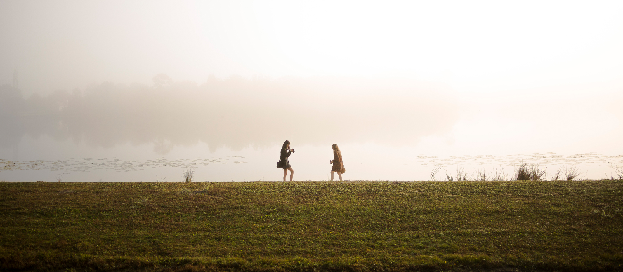 Two Trinity Prep students walk near Lake Burkett with cameras early in the morning as the sun shines though a patch of fog.